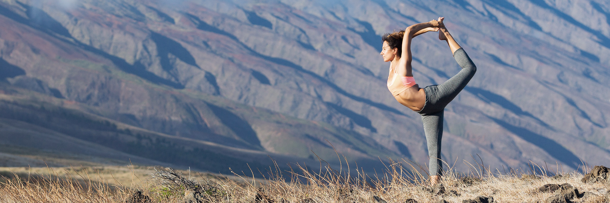 woman doing yoga with mountain in background