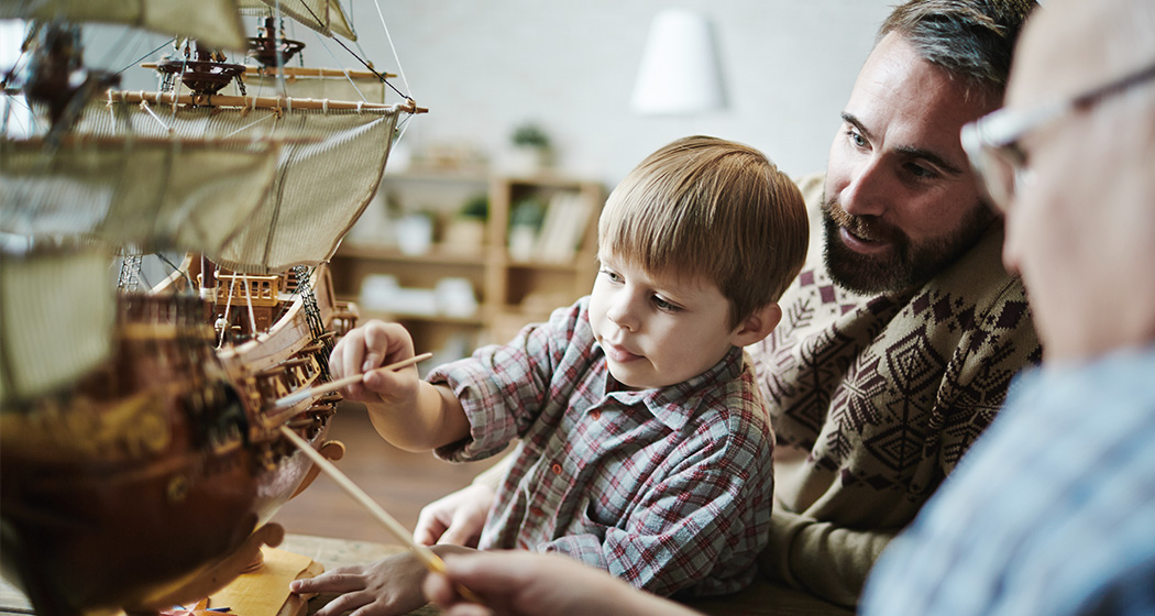 boy playing with model ship with father and grandfather