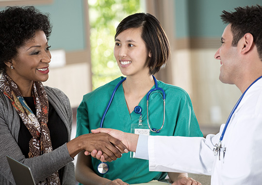woman shaking hands with doctor and nurse
