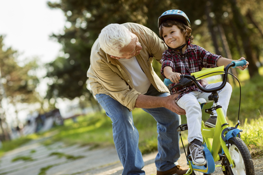 granfather helping grandchild ride a bike
