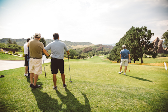 Golfers watching a tee off.
