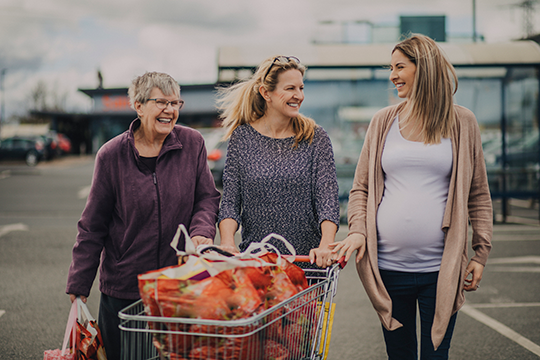 grandma, mom and pregnant daughter grocery shopping