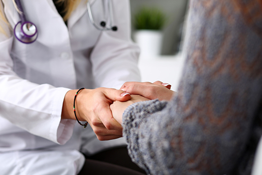 Physician holding patient's hand